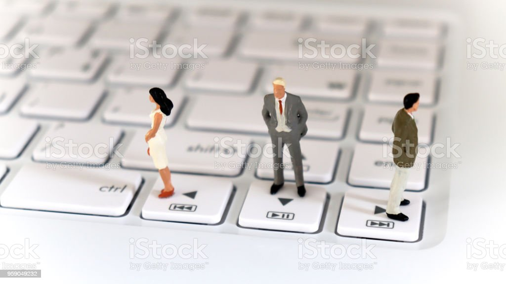 Two miniature men and one miniature woman standing on a keyboard in the other direction. stock photo