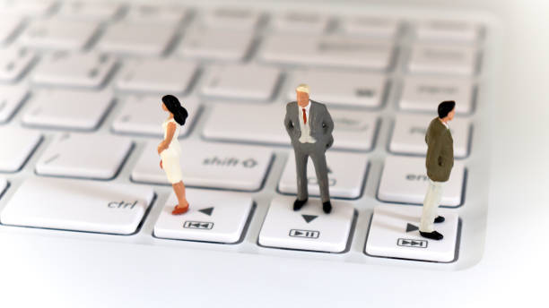 Two miniature men and one miniature woman standing on a keyboard in the other direction. Two miniature men and one miniature woman standing on a keyboard in the other direction. discriminatory stock pictures, royalty-free photos & images