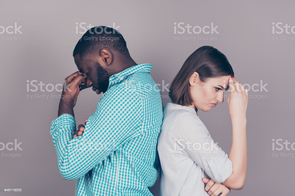 two mixed race people having headaches and stress.  Handsome afro american guy standing together with  his  beautiful caucasian girl two mixed race people having headaches and stress.  Handsome afro american guy standing together with  his  beautiful caucasian girl Adult Stock Photo