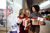 Two mixed race women with gift boxes in hands standing near storewindow. Multi ethnic girls smiling with presents on christmas new year sale. Caucasian and african american females buy presents for holidays.