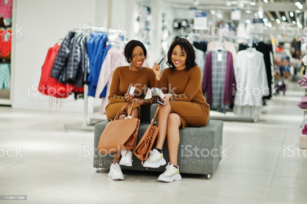 Two models african american woman in brown tunic dress sitting at...