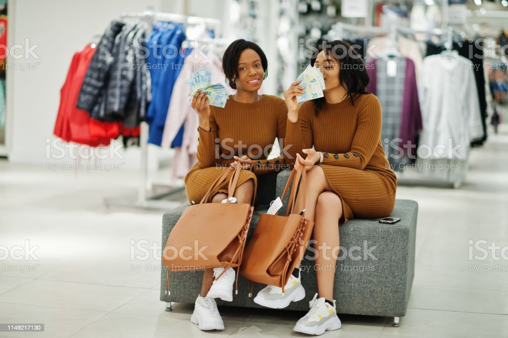 Smell of cash. Two models african american woman in brown tunic dress...