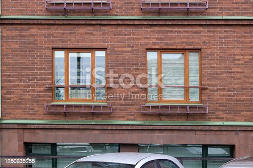 178842131 istock photo Two modern red plastic windows in a red brick   house wall 1250635255