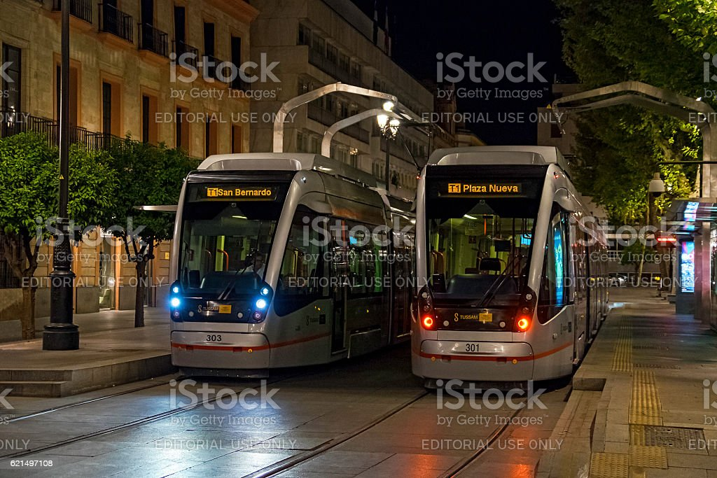 Two modern trams in historic Seville town centre at night photo libre de droits