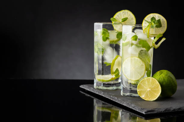 Two mojito cocktails Glasses of cold mojito cocktail with white rum, lemon juice and tonic decorated with lime slices and mint leaves. Focus on the closer glass lemon juice stock pictures, royalty-free photos & images