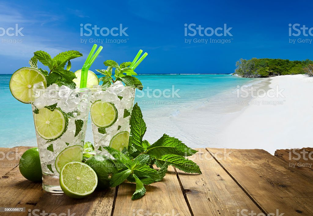 Two mojito cubano drinks against tropical beach stock photo