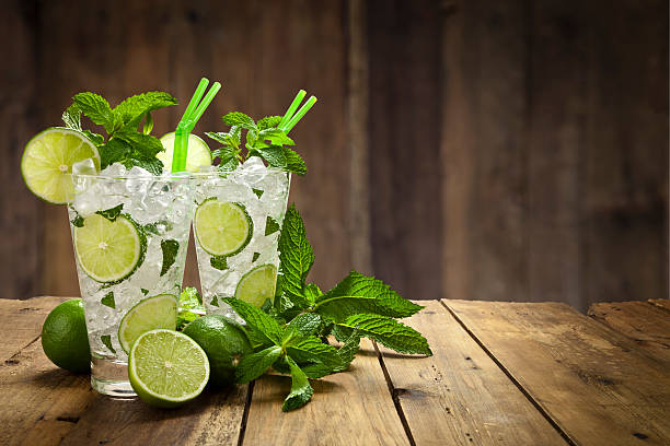 Two mojito cubano drinks on rustic wood table Two mojito cubano drinks on rustic wood table mojito stock pictures, royalty-free photos & images