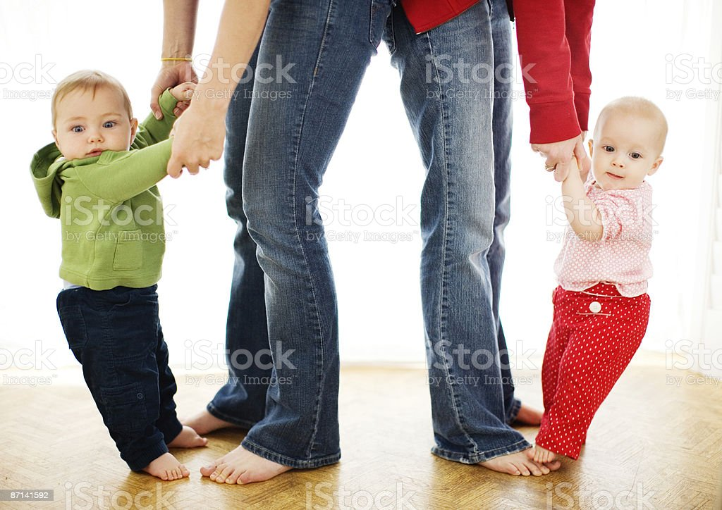 Two moms teaching babies to walk royalty-free stock photo