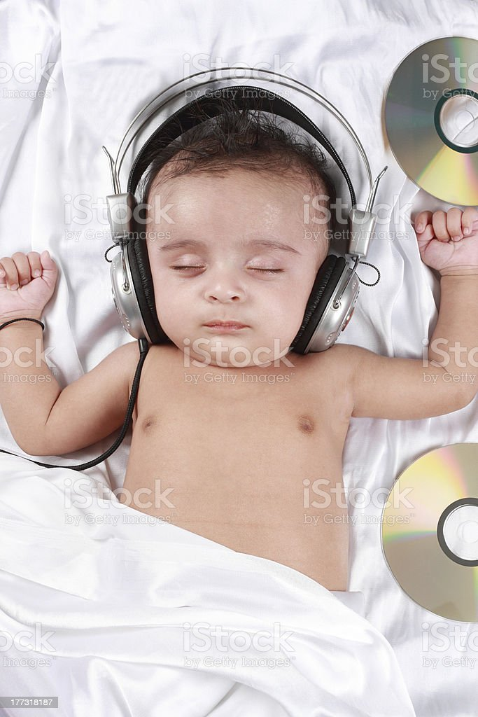 Two Month old baby listening to music with headphones stock photo