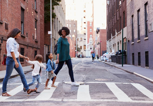 Two mother friends with two daughters crossing the road stock photo