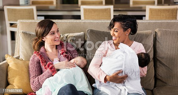 Two multi-ethnic mothers with their 2-3 month old babies, sitting on a sofa side by side, nursing. The African-American woman has a baby boy, and her friend has a baby girl.