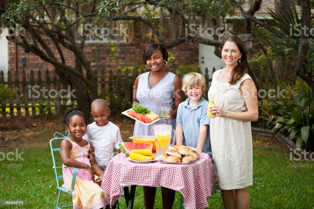 Two mothers and children at backyard cookout stock photo