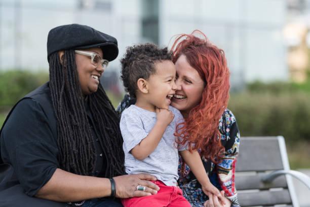 twee moeders houden van hun zoon op hun rondjes buiten in het park - lesbische stockfoto's en -beelden