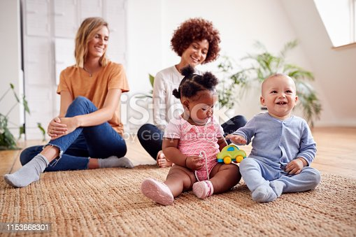 istock Two Mothers Meeting For Play Date With Babies At Home In Loft Apartment 1153668301