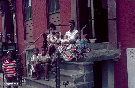 New York City, NY, USA, 1962. Two mothers with their children sitting on the stairs in front of their tenement.