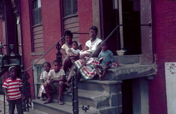 twee moeders met hun kinderen zittend op de trap in de voorkant van hun huurkazerne, new york city - archiefbeelden stockfoto's en -beelden