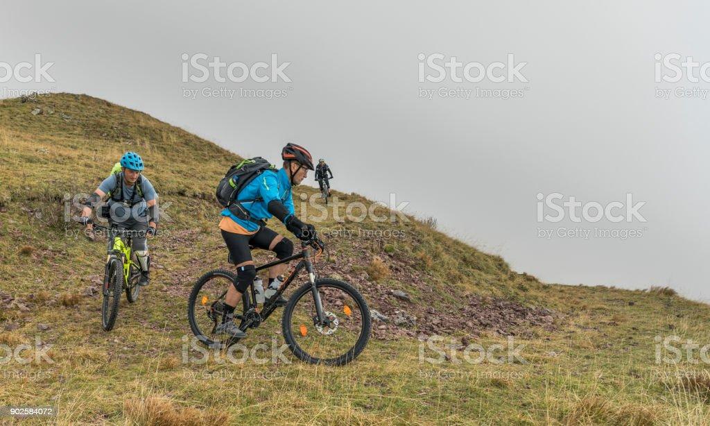 Two mountainbikers taking a hairpin turn in the friulian Mountains, Italy. stock photo