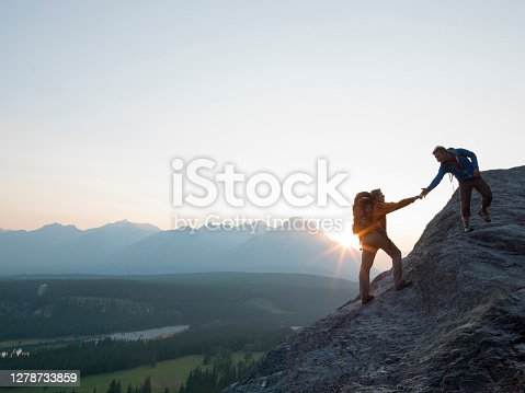 istock Two mountaineers offer helping hand on a rock ridge at sunrise above a valley 1278733859