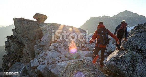 603993820 istock photo Two mountaineers traverse summit ridge at sunrise 1180250427