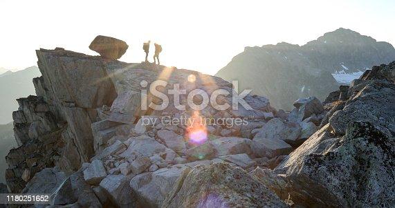 603993820 istock photo Two mountaineers traverse summit ridge at sunrise 1180251652