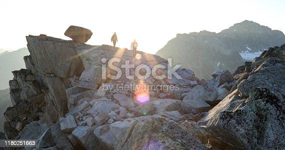 603993820 istock photo Two mountaineers traverse summit ridge at sunrise 1180251663
