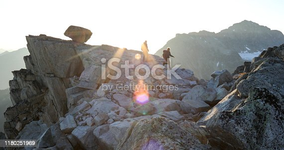 603993820 istock photo Two mountaineers traverse summit ridge at sunrise 1180251969