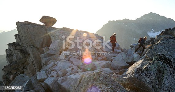 603993820 istock photo Two mountaineers traverse summit ridge at sunrise 1180252067