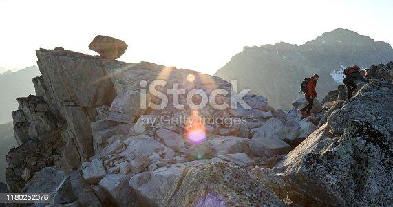 603993820 istock photo Two mountaineers traverse summit ridge at sunrise 1180252076
