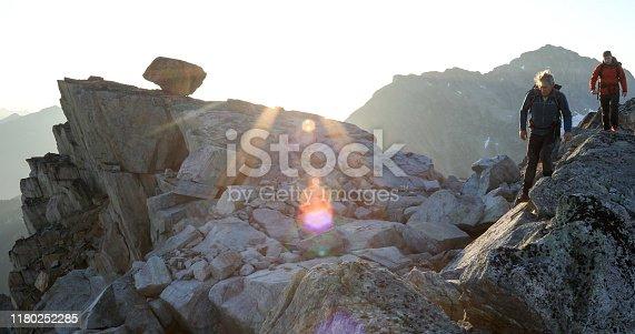 603993820 istock photo Two mountaineers traverse summit ridge at sunrise 1180252285