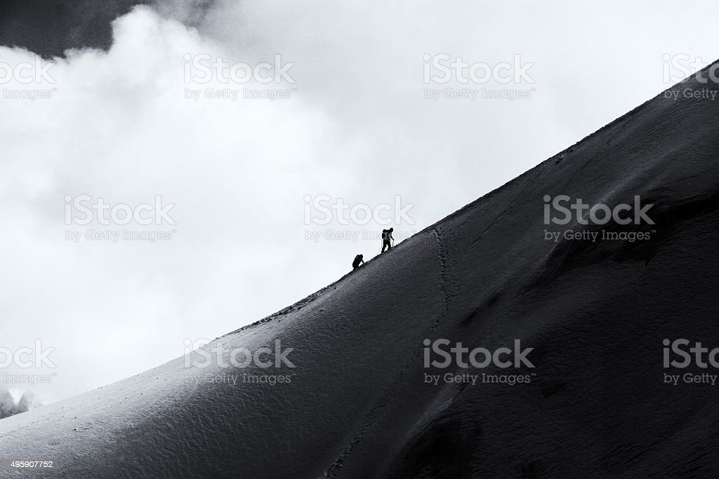 Two mountaineers walking across Mont Blanc high mountain range n stock photo
