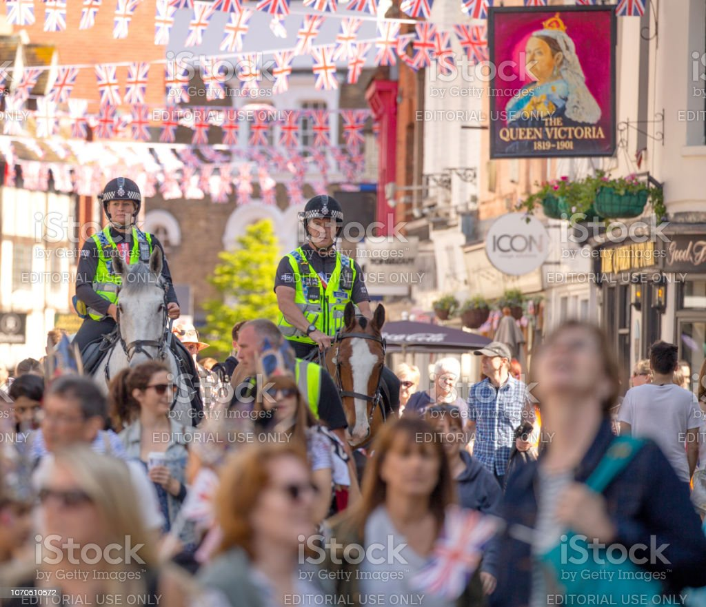 Two mounted police officers marshalling the crowds of people on their way to celebrate the marriage of Meghan Markle and Prince Harry at St George's Chapel at Windsor Castle - Стоковые фото Duchess of Sussex роялти-фри