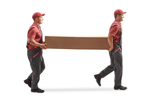 Two movers carrying a big cardboard box Full length profile shot of two movers carrying a big cardboard box isolated on white background carrying stock pictures, royalty-free photos & images