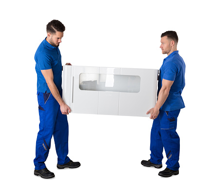 Two Movers Holding Furniture In Living Room