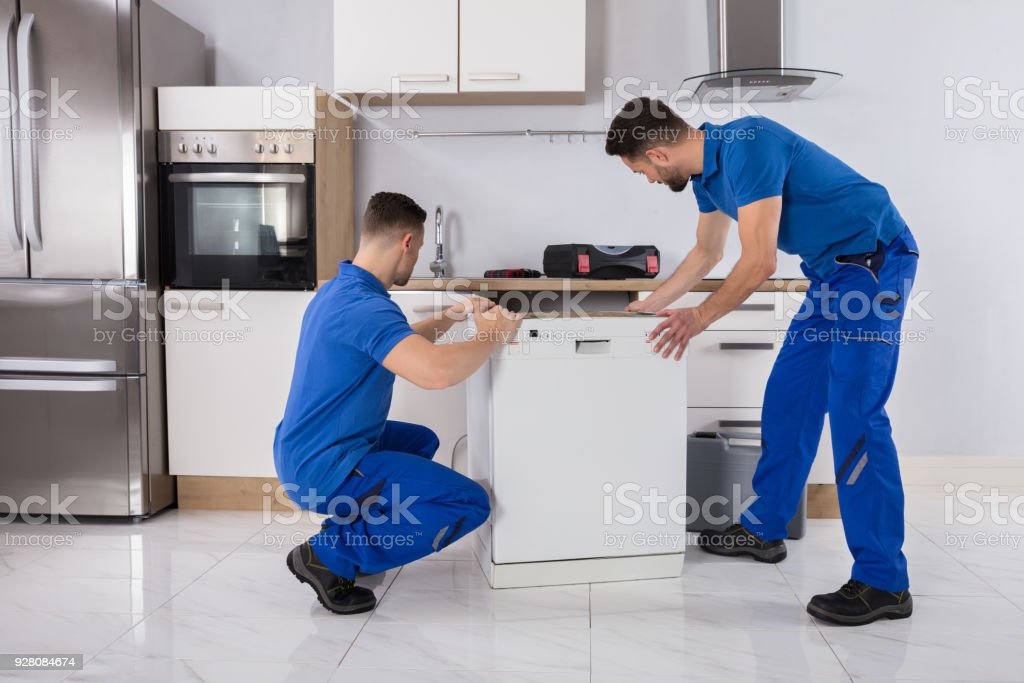 Two Movers Placing Dishwasher In Kitchen stock photo