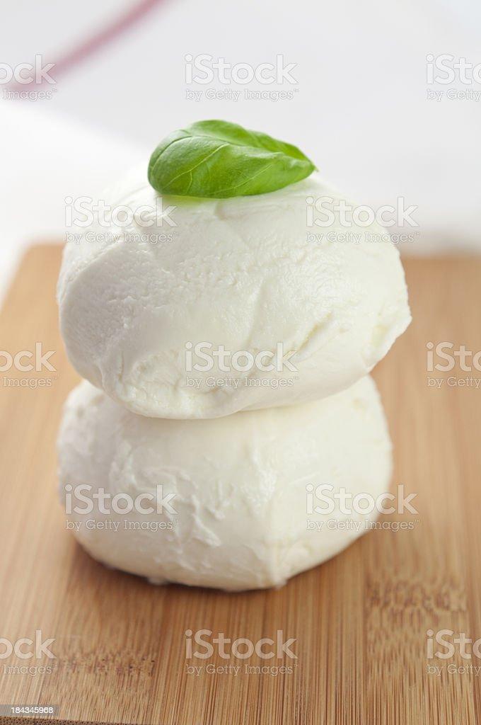 Zwei Mozzarella-Kügelchen in einem kleinen Schneidebrett – Foto