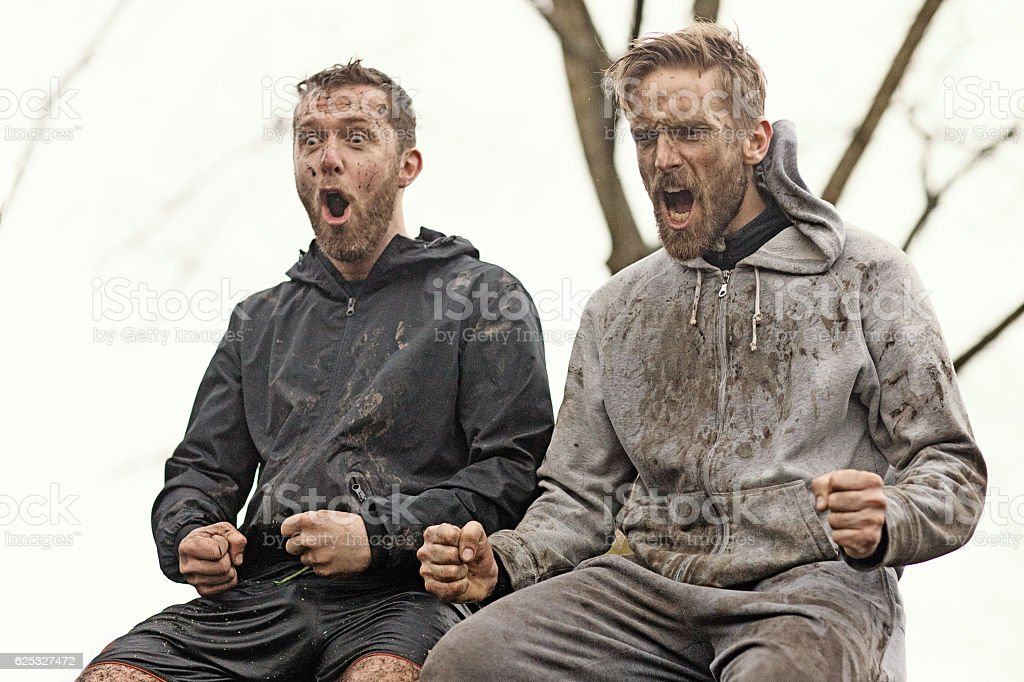 Two mud run teammates yelling sitting together on wall obstacle stock photo