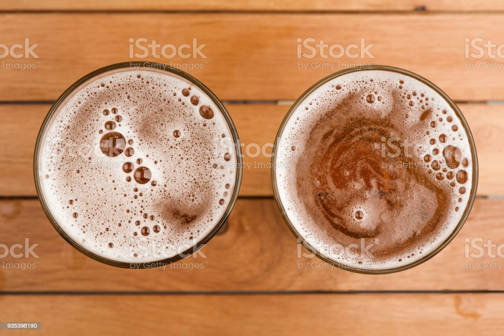 Two mug of beer with bubble on glass on top view wooden background stock photo