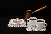 Two mugs of coffee, Turkish delight and cherry pots on a black background