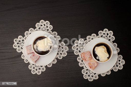 Two mugs of coffee with ice-cream, Turkish delight on a saucer, on white lace napkins. Top view, black background