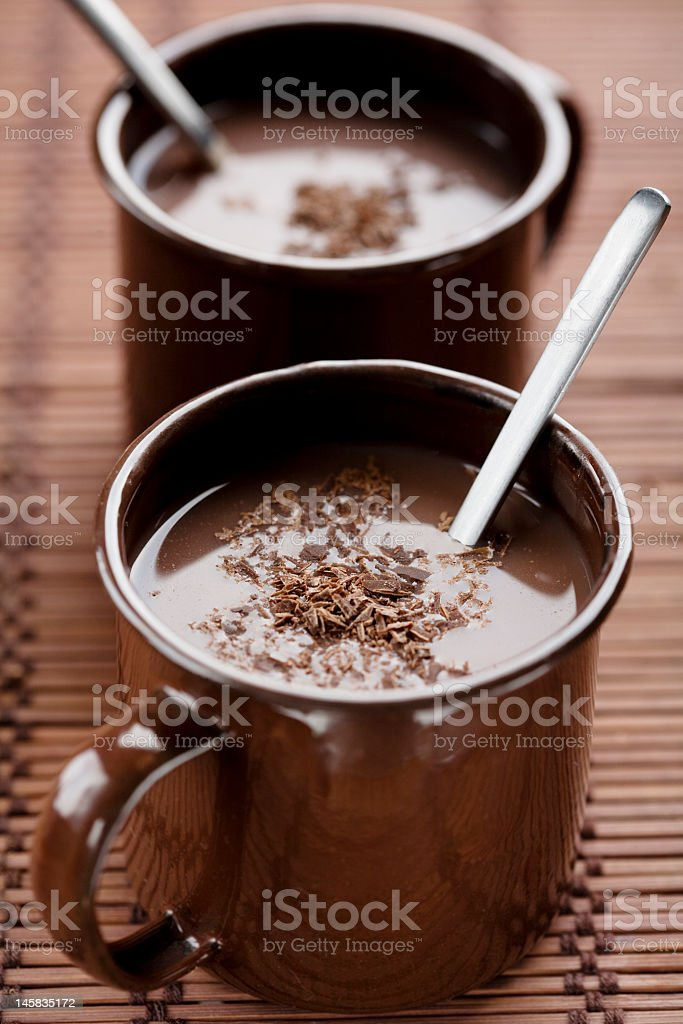 Two mugs with a spoon and chocolate pieces on top royalty-free stock photo