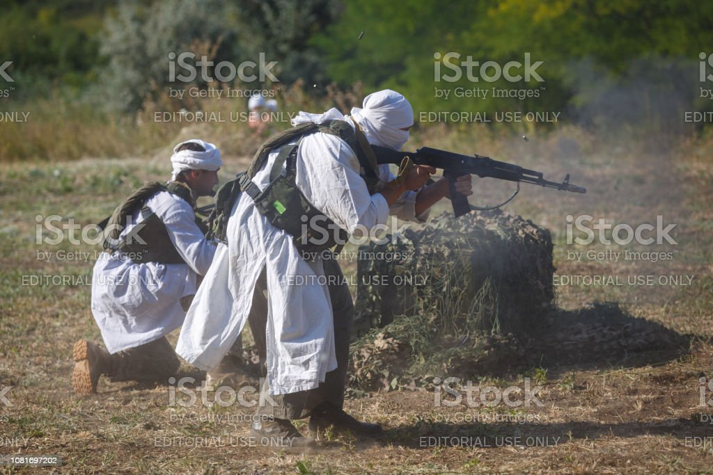 Two mujahideen shoot from behind intrenchment stock photo