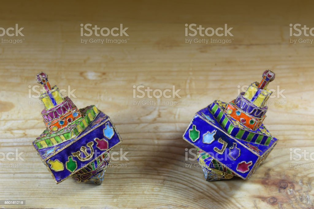 Two multicolored Hanukkah dreidels on a wood tabletop with space for text stock photo