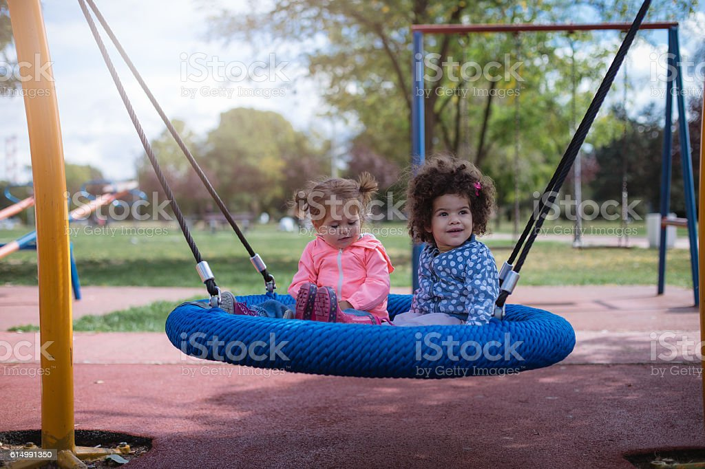 two multicultural babies playing on a swing in park stock photo