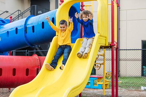 Two multi-ethnic boys sliding down playground slide