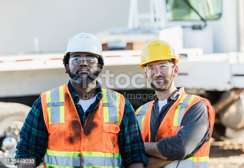 Two multi-ethnic mid-adult men in their 30s, construction workers at a job site. They are wearing hardhats, reflective vests and safety glasses, standing in front of a crane.