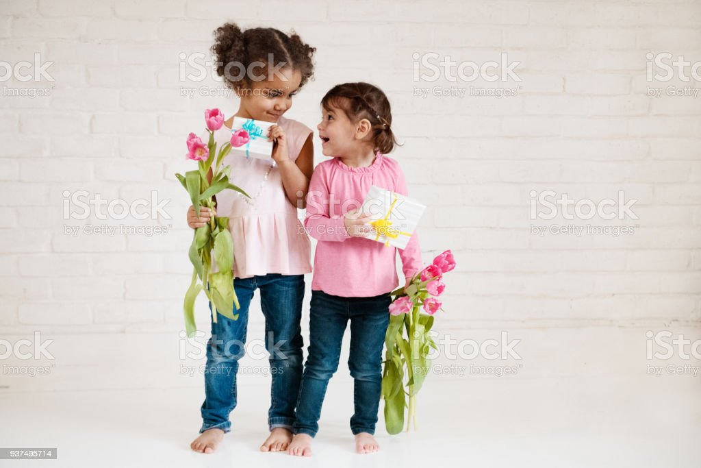 Two Multi-ethnic little girls holding gifts and tulips for mother's day stock photo