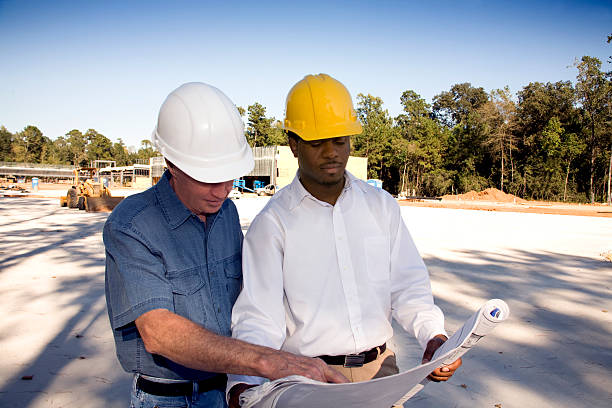 Two multi-ethnic men in hardhats at construction site with blueprints. stock photo