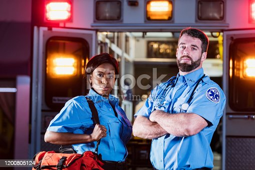 Two young multi-ethnic paramedics at night, standing by the back doors of an ambulance with lights flashing. The African-American woman and her male coworker are looking at the camera with serious expressions. She is carrying a medical trauma bag.