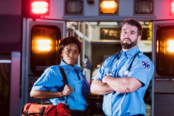 Zwei multiethnische Sanitäter mit Krankenwagen – Foto