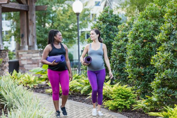 Zwei multiethnische Schwangere gehen zum Yoga-Kurs – Foto